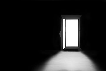 Abstract image of Light shining through opened door in dark room.