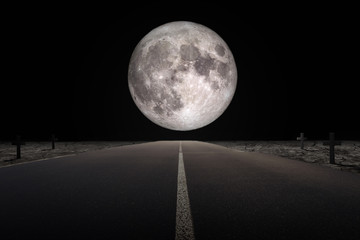 Halloween Concept : Empty road leading to full moon flanked with tomb in dark night. (Elements of this image furnished by NASA.)