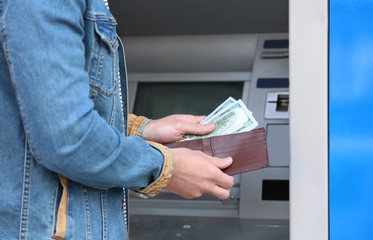 Man with money near cash machine outdoors, closeup