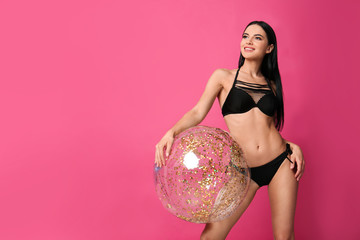Beautiful young woman in stylish bikini with beach ball on pink background. Space for text