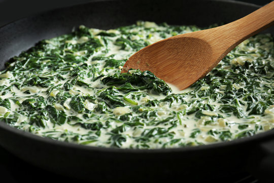 Tasty spinach dip with wooden spoon in frying pan, closeup view