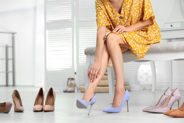 Woman trying on different shoes indoors, closeup Wall mural