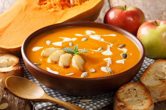 Traditional autumn pumpkin and apple soup with seeds close-up in a bowl on the table. horizontal
