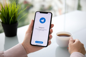 Woman hand holding iPhone X with social networking service Telegram