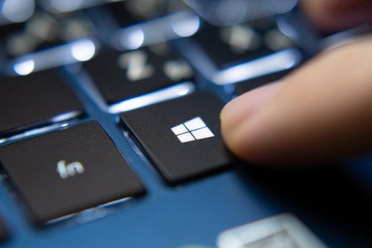 Bangkok, Thailand - July 13, 2019 : Laptop user pressing Windows Key on Microsoft Windows keyboard.