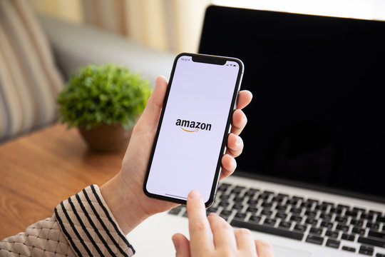 Woman holding iPhone X with Internet shopping service Amazon