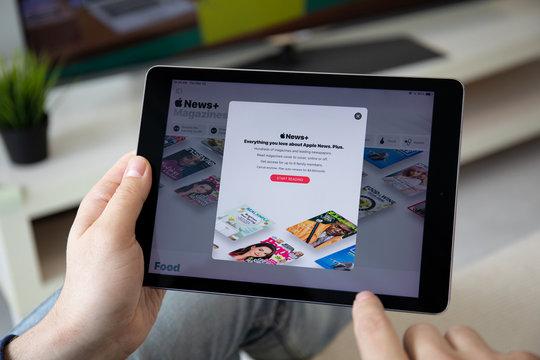 Man holding iPad Pro with service Apple News +