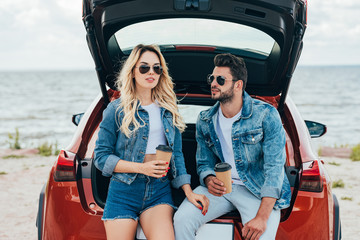 Fotomurales - attractive woman and handsome man in denim jackets holding paper cups