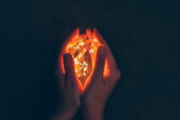 Woman hand holding illuminated garland in her hands in dark