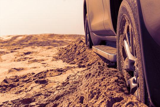 Car wheels on a sea beach sand. Close-up of car wheel on sandy dunes. Car stuck in the sand. Spinning wheel of a car stuck in the sand.