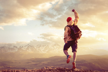 Happy man jumps in winner pose against sunset mountains Wall mural