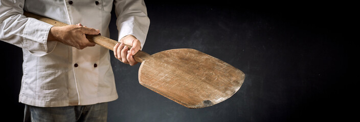 Cook or chef in a pizzeria with a wooden paddle