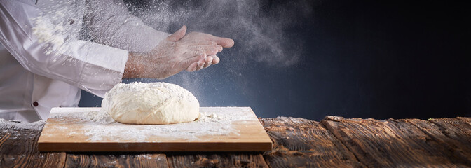 Foto op Plexiglas Bakkerij Chef or baker dusting dough with flour
