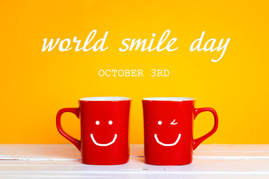 World smile day card with two red coffee mugs with a smiling faces on a yellow background.  For greeting card, poster and banner.