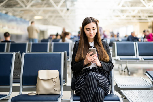 Young woman using mobile phone at airport
