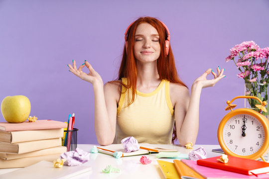 Photo of relaxed student girl in headphones sitting at desk with exercise books