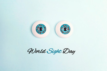 World sight day poster with decorative eyes on a blue background.