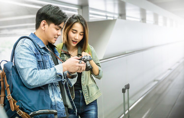 Portrait of beautiful asian couple man woman holding camera in the airport. Young happy travelers couple looking on camera. Tourist people lifestyle happy honeymoon concept.