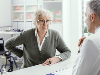 Senior lady with back pain in the doctor's office