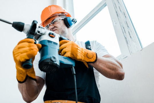 low angle view of handyman in helmet and yellow gloves using hammer drill