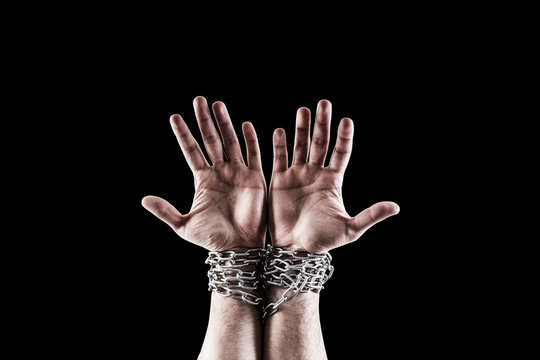 Two hands in chains isolated on black background with clipping path