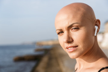 Image closeup of cute bald woman using earphones and looking at camera