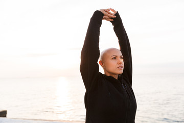 Image of focused bald woman looking upward and stretching arms