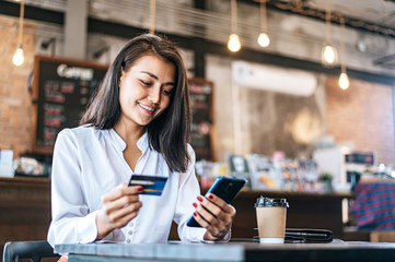 Pay for goods by credit card through a smartphone in a coffee shop.