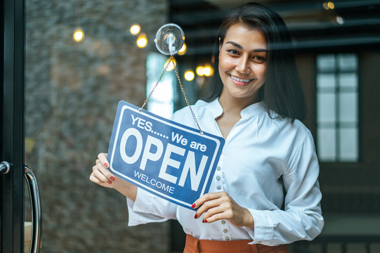 woman stands and opens a wide sign through the shop window and smile.