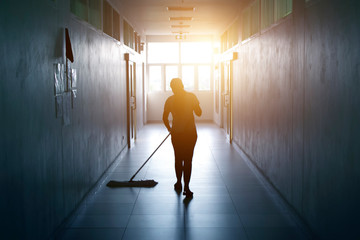 Janitor woman mopping floor in hallway office building or walkway after school and classroom silhouette work job with sun light background.