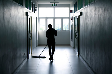 Janitor woman mopping floor in hallway office building or walkway after school and classroom silhouette work job background.