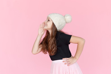 A cute little girl in a woolen cap, stands in profile and whispers secrets, over pink background, with copy space.