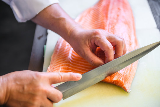 close up chef cutting fresh salmon