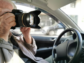 Private investigator with digital camera making photographs in car