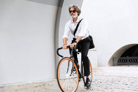 Photo of caucasian old businessman riding bicycle on city street