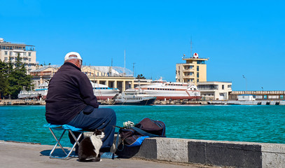 Old man is fishing at the city promenade with a cat sitting nearby him.