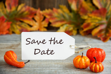 White Label With English Text Save The Date. Wooden Background With Autumn Decoration Like Pumpkin And Leaves