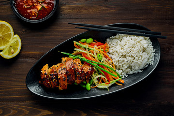 Traditional Japanese teriyaki chicken with salad made of cucumber, ginger, carrot, pepper and cabbage, rice, sesame,edamame, lemon and sweet chili sauce on a rustic table. Top view, directly above.