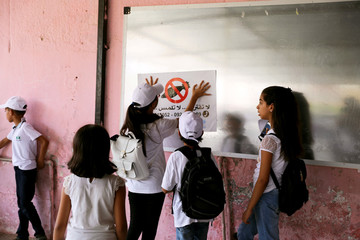 Libyan students look at warning sign during the summer school programme at Ben Ashour school in Tripoli