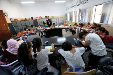 A group of young children set around a table practice drawing and calligraphy skills during the summer school programme at a local school in Tripoli