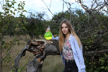 A cute girl in a man's shirt holds a flask with green fluorescent substance, put it on an old fallen apple tree. Wall mural