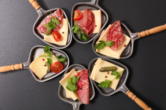 assorted of spoon with cheese raclette, salami and tomato