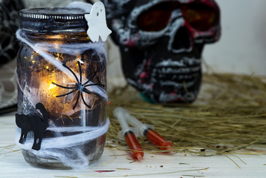 Jar filled with orange string lights in spooky room full in a black jar with a web and a spider on a dark background