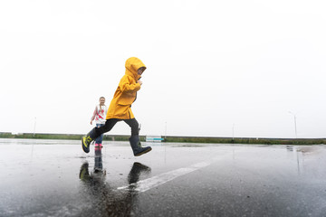 A little boy in a yellow raincoat jumps through puddles in the rain.