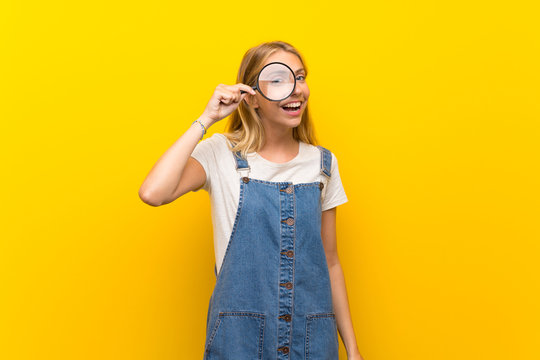 Blonde young woman over isolated yellow background holding a magnifying glass