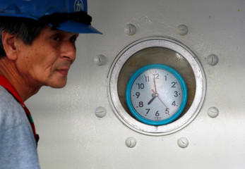 A fisherman passes a clock onboard their fishing vessel at the Ofunato fish market in Ofunato