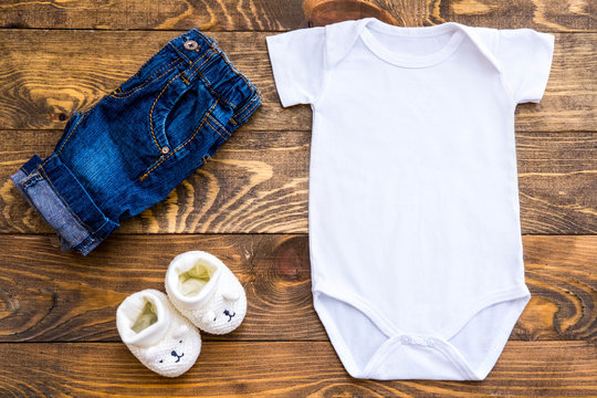 Mockup of white baby bodysuit shirt, slippers and jeans