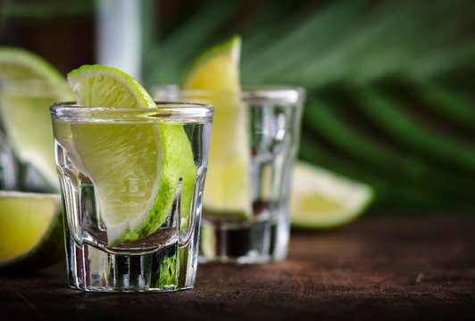 Cachaca - Brazilian strong alcoholic beverage from cane sugar, lime vodka, vintage wooden background, selective focus