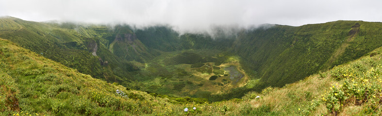 Rain clouds hanging over the rim of the luscious green Caldera of the central crater on Faial island on a stormy sunny day in the Azores.