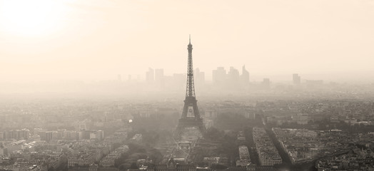 Aerial view of Paris with Eiffel tower and major business district of La Defence in background at sunset. Sepia toned monocrome image.